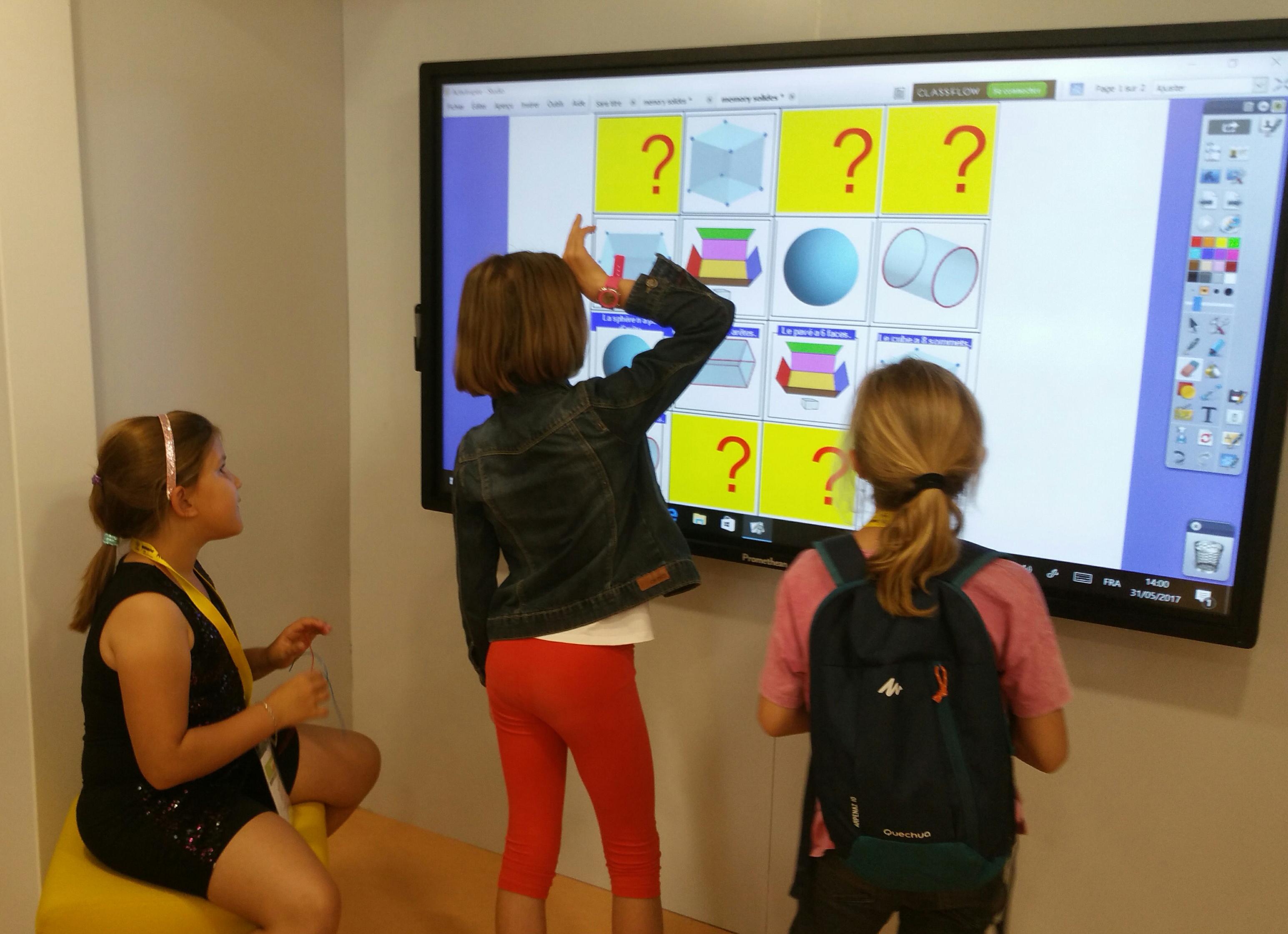 Enfants essayant un des ateliers du bus numérique
